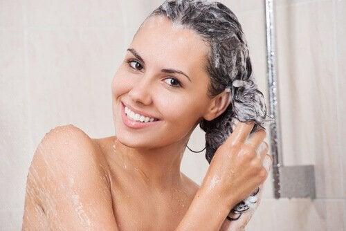 kvinne vasker håret med sjampo for personlig hygiene
