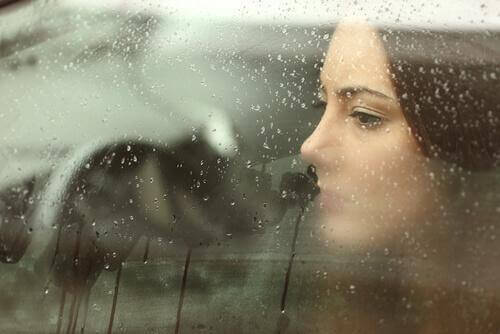 Trist kvinne bak vindu med regn