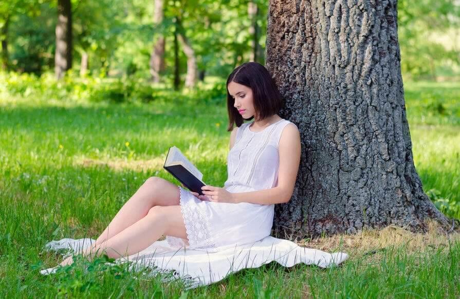 Kvinne leser bok under et tre