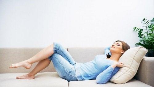 Dame som slapper av i sofaen
