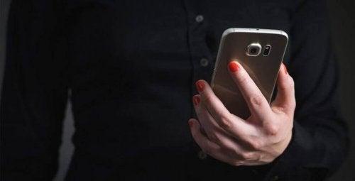 kvinne holder mobiltelefon - null kontakt