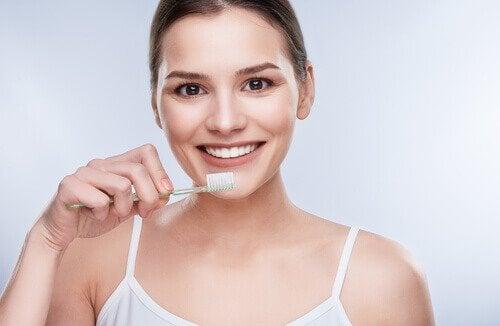 Kvinne pusser tennene med tannkrem med kokosolje