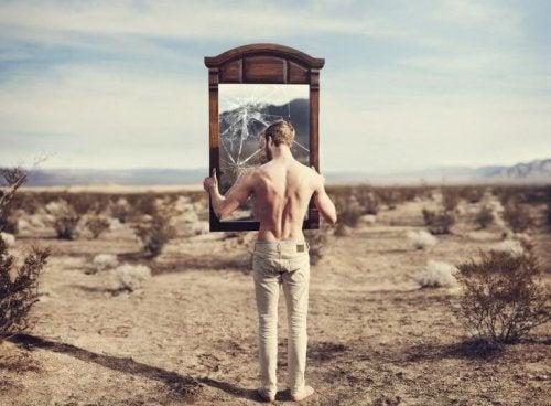 Mann som ser på ødelagt speil