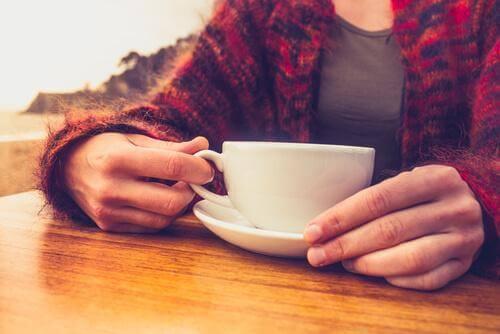 Person med koffeinabstinenser holder kaffekopp