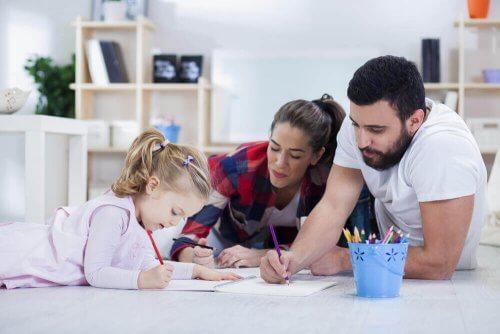 foreldre hjelper datteren med hjemmeleksene