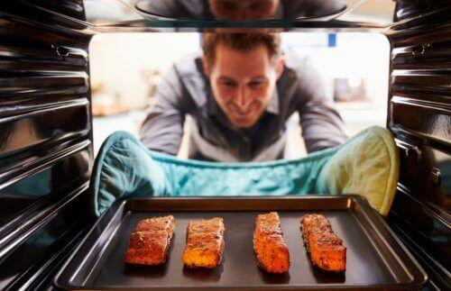 Mann tar ut laks fra ovnen