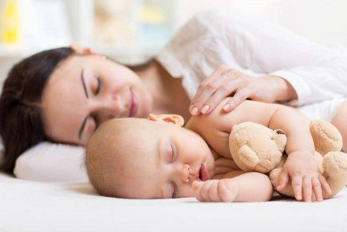 Mor og barn sover i sengen.