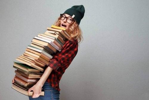 Jente holder en haug med bøker