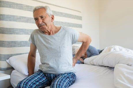 Mann med leddsmerter sitter på sengekanten