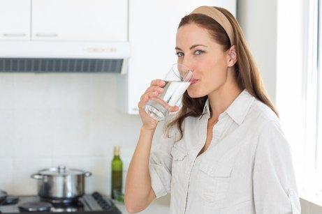 Kvinne drikker vann for å stramme opp huden