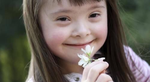 Barn med Downs syndrom lukter på en blomst