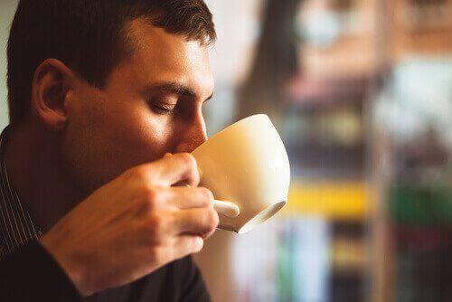 Mann drikker kaffe for å holde seg våken