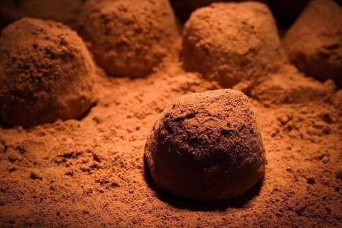 Deilige sjokoladetrøfler på en seng av kakaopulver.