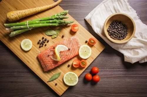 Barns kosthold: Et skjærebrett med laks, asparges, pepperrot, lime, tomater, laurbærblad og en skål med svart pepper på siden.