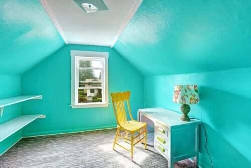 De beste fargene for et barns soverom: Et rom med livlige blå vegger med et skrivebord, en lampe og en gul stol.