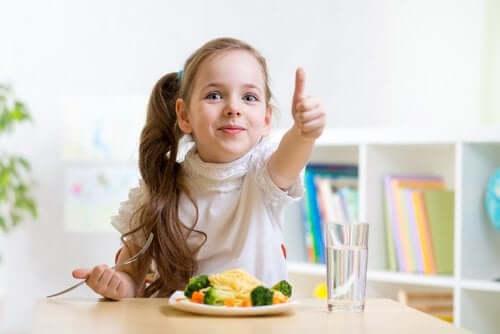 Ditt barns kosthold: En jente som spiser og gir tommelen opp.