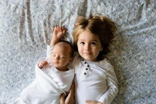 En baby og en liten gutt som ligger i sengen.
