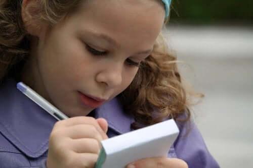 En jente som øver på staving i en notisblokk.