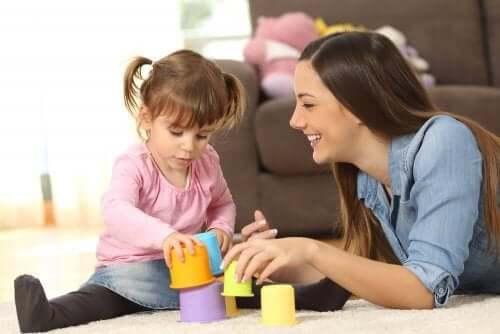 En kvinne og en liten jente som leker på teppet.