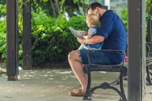 En mann og en baby som ser i en bok.