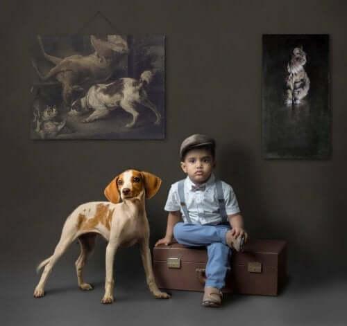 Et barn som sitter på en koffert akkompagnert av en hund med mørk bakgrunn og bilder av dyr.