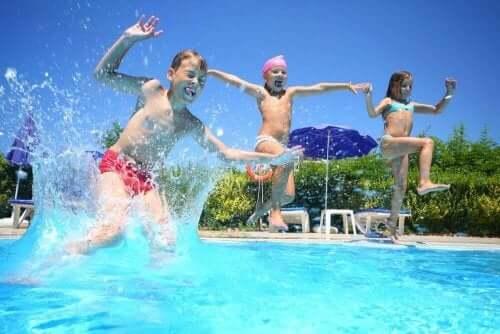 Tre barn som hopper i et basseng, de ser ikke ut til å være overbelastet med aktiviteter.