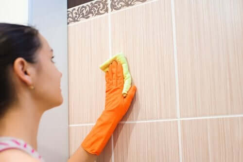 Kvinne rengjører flisvegger.