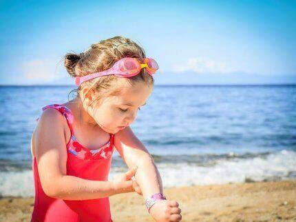 En jente som ser på flekker på armen.