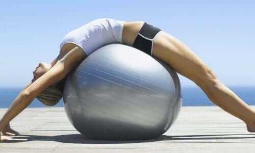 En kvinner som ligger på en pilatesball