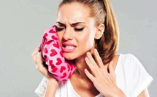 Kvinne som lindrer tannpine med is