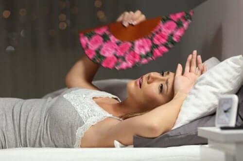 Kvinne med overoppheting bruker en vifte