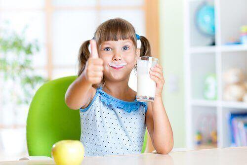 En jente som drikker et glass melk.