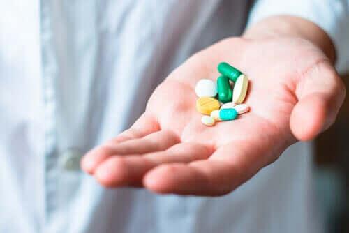 En lege som holder piller av aceklofenak.
