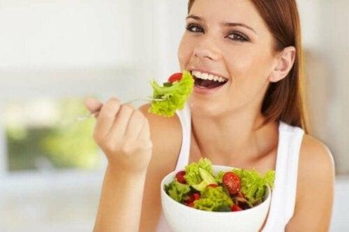 En kvinne som spiser salat