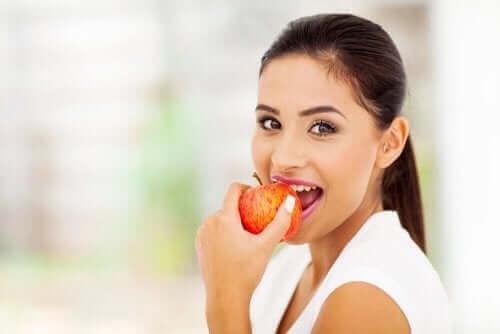 En kvinne som spiser et eple.