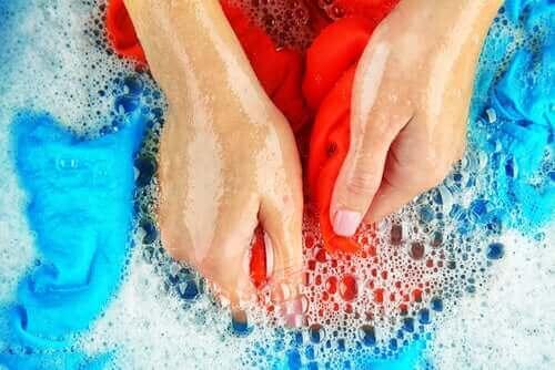 En kvinne vasker klær for hånd.