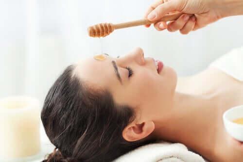Kvinne som blir behandlet med honning i ansiktet.