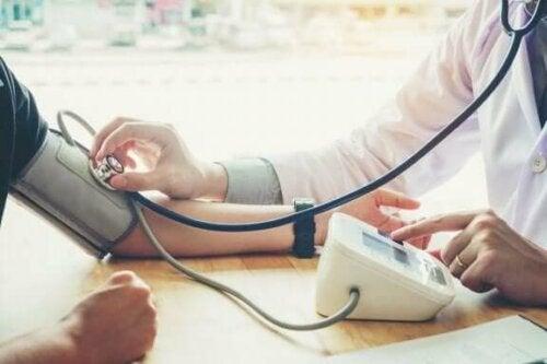 En lege som bruker en blodtrykksmåler på en pasient