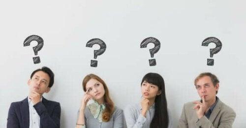 Fire personer med spørsmålstegn over hodene sine