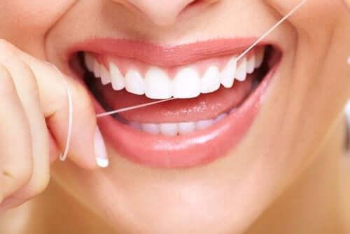 Kvinne som bruker tanntråd.