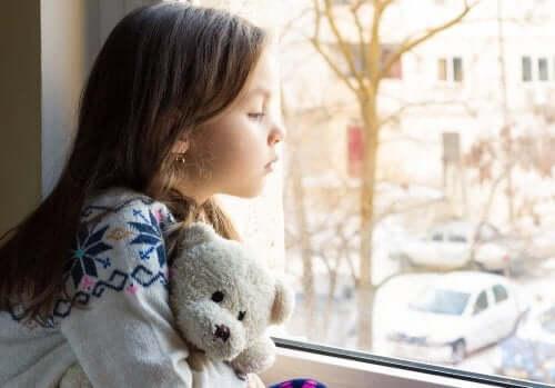 liten jente som kikker ut av vinduet