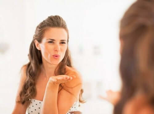 En kvinne som sender et slengkyss til speilbildet sitt