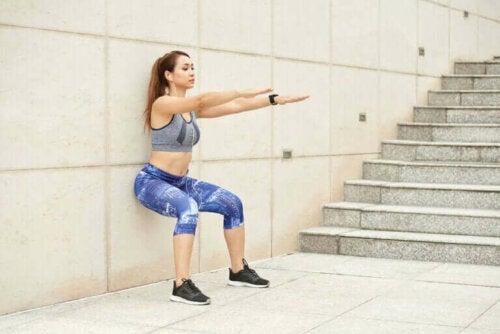 Kvinne gjør knebøy mot veggen for å holde seg i form uten å dra hjemmefra