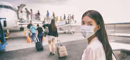 Kvinne med maske går på et fly