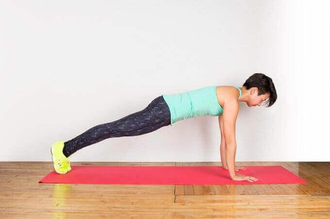 Kvinne gjør planken for å holde i form uten å dra hjemmefra