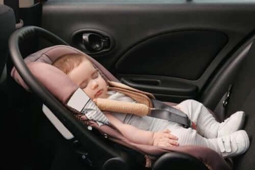 En baby som sover i en bil, ubekymret for deformasjonsplagiocefali.