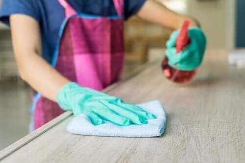 En kvinne som bruker avfettingsmiddel for å rengjøre tremøblene sine.