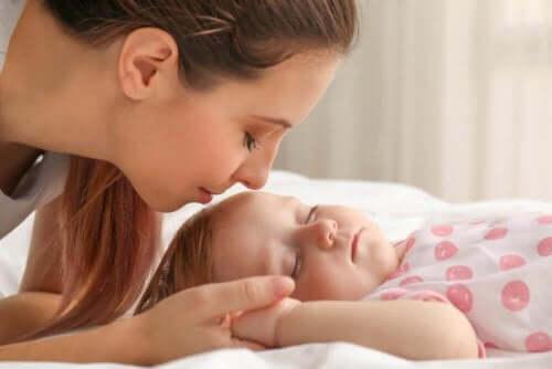 En kvinne som er i ferd med å kysse en baby.