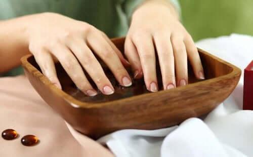 En kvinne som har neglene i hvitløksvann.