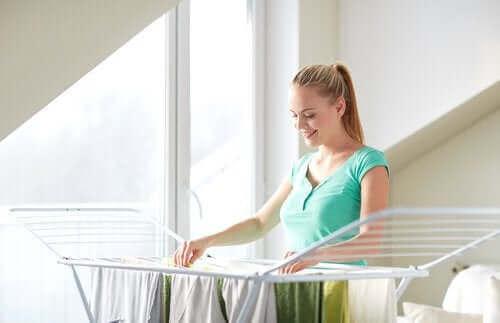 En kvinne som henger klærne sine for å tørke.